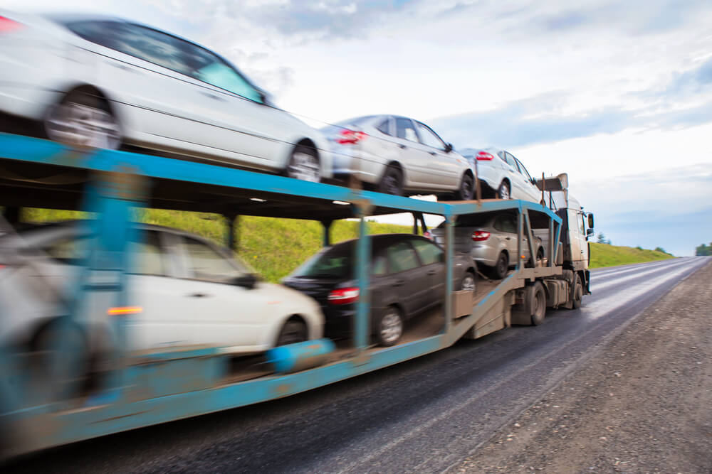 Transporter with cars in the back, on white background.